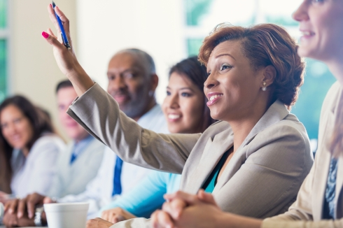 African American businesswoman raising hand, asking question in business conference
